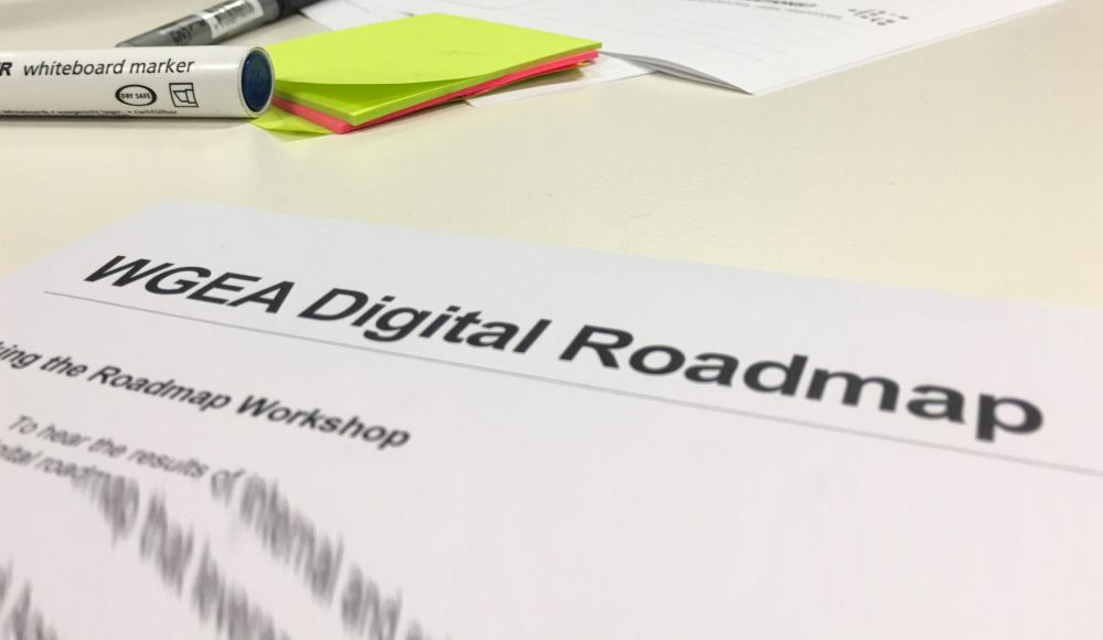 "Image of area of tabletop with markers and sticky notes and part of a page titled ""WGEA Digital Roadmap"""